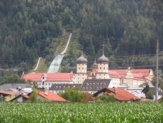 Klostret Stift Stams med en skihopbakke bagved/The monastery Stift Stams and a ski jumping hill
