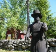 En træmand uden for kirkegårdsmuren/Wooden fellow outside the churchyard wall