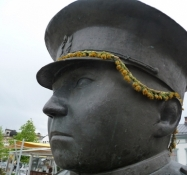 Sommerpyntet, men mut torvepolitimand/Summerly decorateded but sultry market place policeman