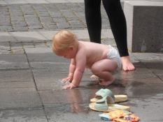 Baby leger med vand på torvet i Rudkøbing/Toddler plays with water on the Rudkoebing market place