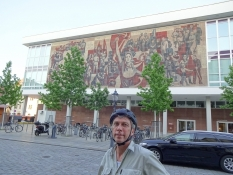 Well arrived in Dresden, Kolya is standing in front of a GDR-style murial painting