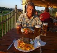 Having supper at an outdoor restaurant down by the riverside