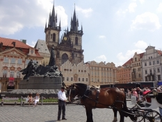On the old cityʹs city hall square with the Jan Hus monument and the Týn cathedral