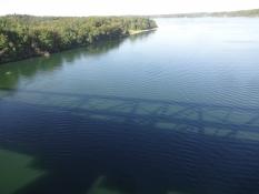 Ein Blick von der Brücke mit ihrem Schatten auf der Wasseroberfläche